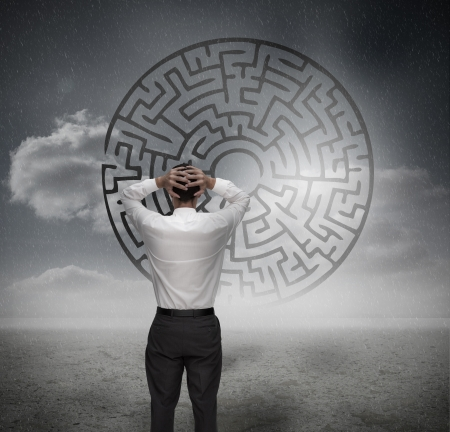 Anxious businessman looking at maze in dull grey landscape Stock Photo - 20630229