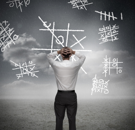 Anxious businessman losing at noughts and crosses with hands on head photo