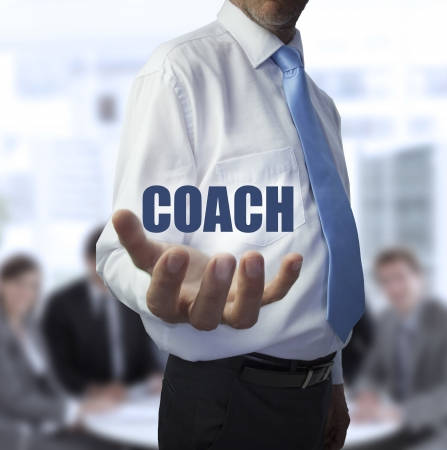 Smart businessman holding the word coach in front of a business team photo