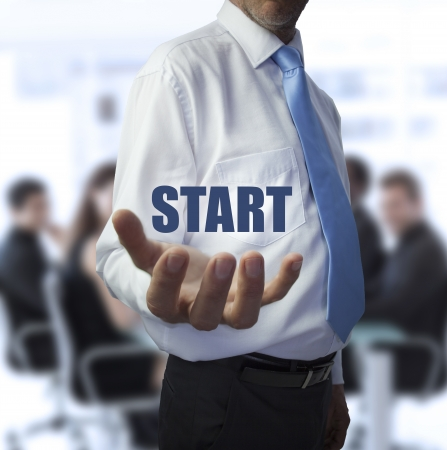 Businessman holding the word start in front of a business team photo