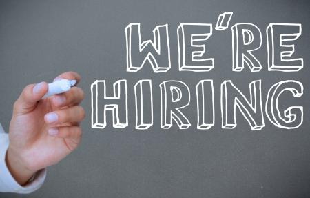 recruit: Hand writing were hiring on grey background