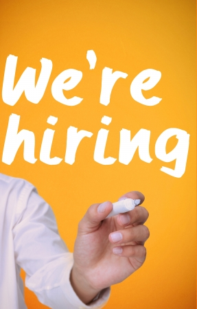 recruit: Businessman writing were hiring with a marker on yellow background