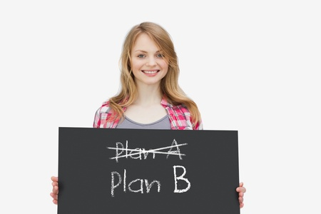 plan b: Smiling girl holding a blackboard with plan a and plan b written on it