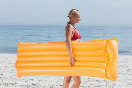 Woman walking on beach with her lilo