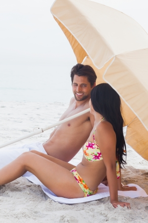 Couple in holiday speaking together on beach towel  photo