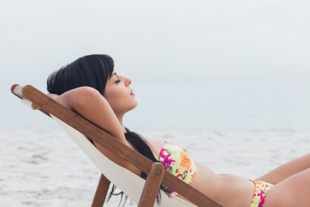 Beautiful woman sleeping on deck chair on beach photo