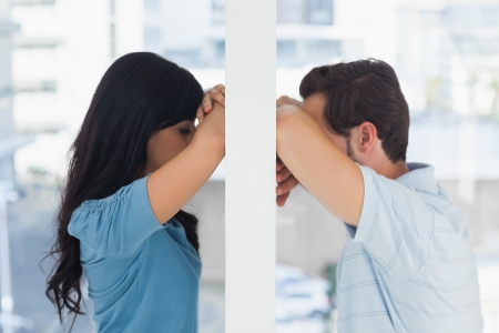 pessimistic: Depressed couple divided by wall