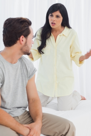 reprimanding: Woman reprimanding her boyfriend in bedroom Stock Photo