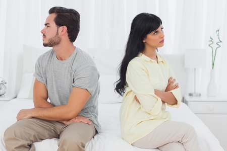 outraged: Couple sulking with arms crossed in bedroom