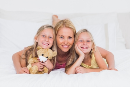 Portrait of a blonde woman in bed with her children photo