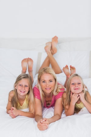 Cute twins lying with their mother in bed