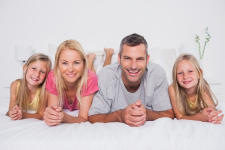 Parents lying in bed with their cute children photo