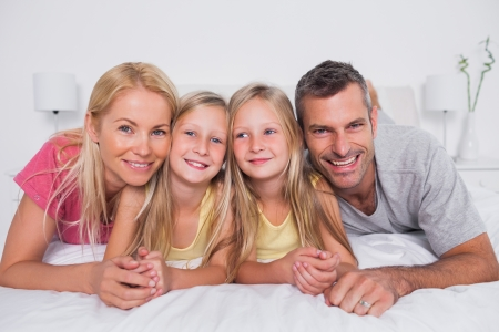 Portrait of parents lying in bed with their cute children photo