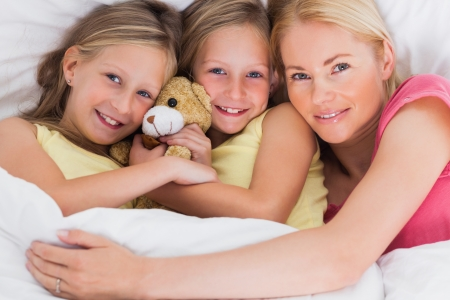 Blonde woman napping in bed with her cute children photo