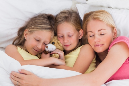 Blonde woman sleeping in bed with her cute children photo