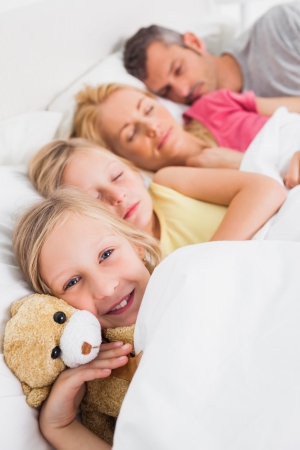 Young girl awake next to her sleeping family in bed photo