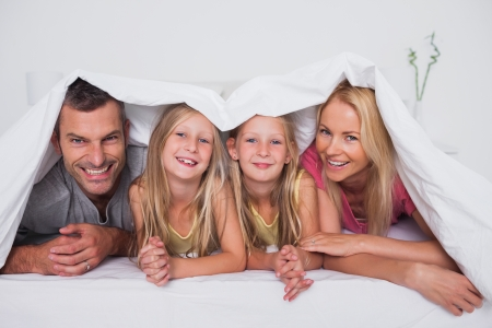 Family playing under the quilt in bed photo
