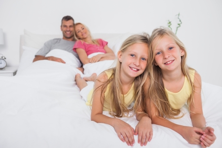 Twins posing in bed in front of their parents smiling on the background photo