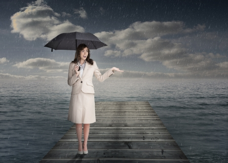 Elegant businesswoman holding an umbrella in front of the sea photo