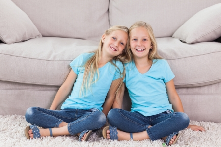 Twins sitting on a carpet in the living room photo