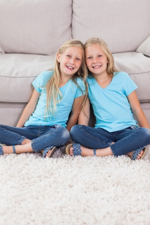 Young twins sitting on a carpet in the living room photo
