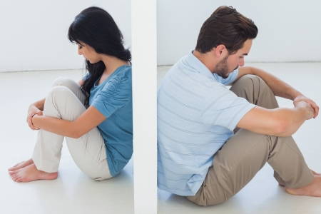 divided: Sitting couple are separated by white wall and looking depressed