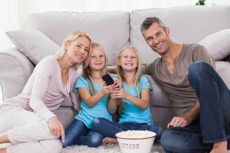 Twins and parents eating popcorn and watching television sitting on a carpet photo