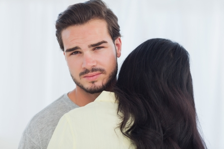 uninterested: Woman giving hug to uninterested boyfriend looking at camera