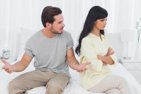 couple talking: Woman sulking while her boyfriend is explaining himself during a fight in bedroom