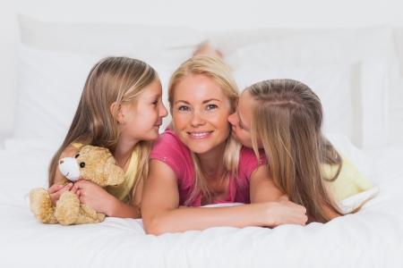 gemelas: Gemelos lindos que besan a su madre en la cama Foto de archivo