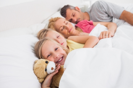Parents sleeping with their cute daughters in bed Stock Photo - 20624492