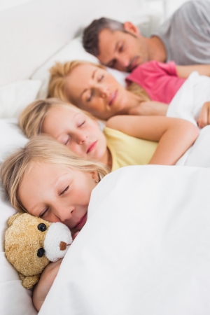 Young girl holding a teddy bear next to her sleeping family in bed photo