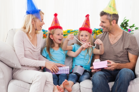 Family wearing party hat and celebrating twins birthday with birthday gift photo