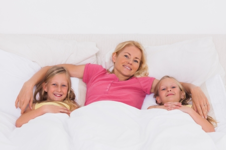Blonde woman lying in bed with her children photo