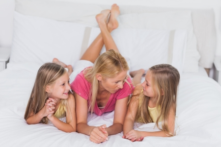 Cute twins relaxing with their mother in bed photo