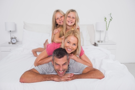 Happy man giving a piggy back to his cheerful family Stock Photo - 20624668
