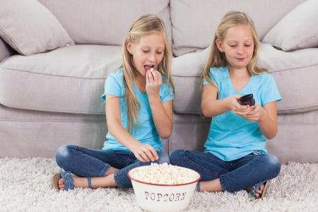 gemelas: Twins comiendo palomitas y viendo la televisión sentado en una alfombra Foto de archivo