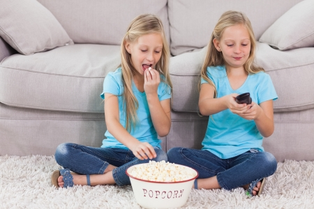twin house: Twins eating popcorn and watching television sitting on a carpet