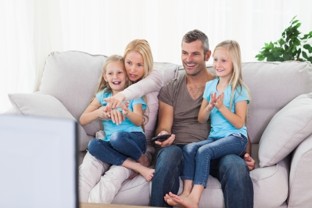 on lap: Cute twins and parents watching television sitting on a couch
