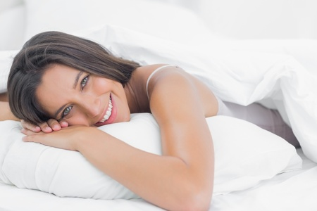 homely: Portrait of a pretty woman relaxing in bed