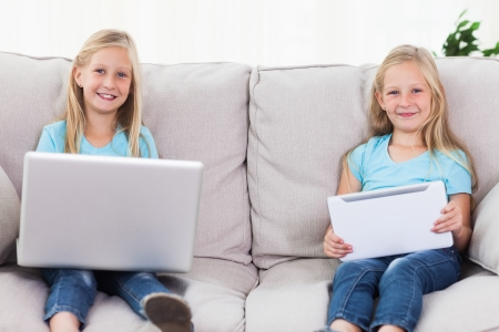 Twins using a laptop and a tablet sitting on a couch in the living room photo