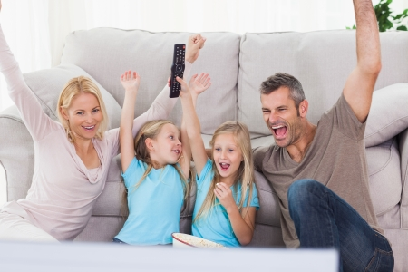 Mellizos y los padres que crían brazos mientras ve la televisión sentado en una alfombra