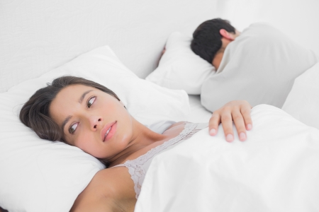 Anxious woman sleeping in bed next to her partner photo