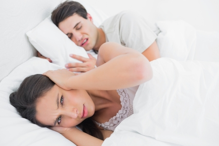 wincing: Woman covering ears while her partner is snoring next to her in bed