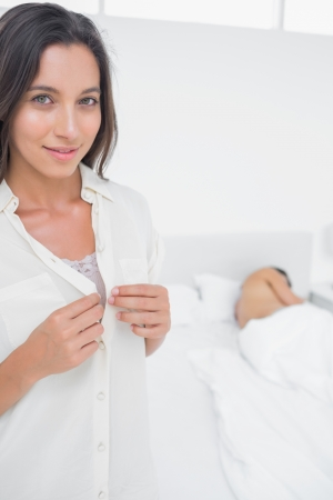 sneaking: Portrait of a woman sneaking out of bed next to an asleep man Stock Photo