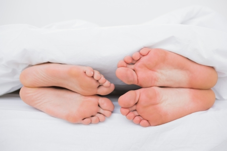 man feet: Feet of a couple sleeping face to face in bed  Stock Photo