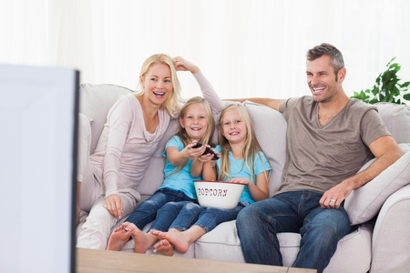 popcorn bowls: Twins and parents watching television sitting on a couch