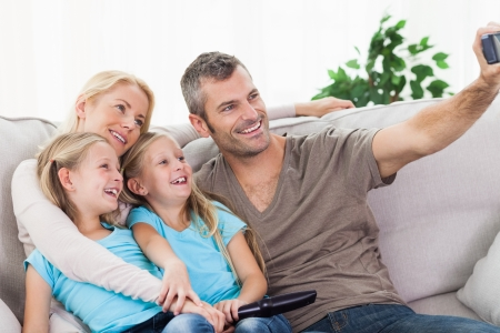 Man taking picture of his children and wife sitting on a couch photo