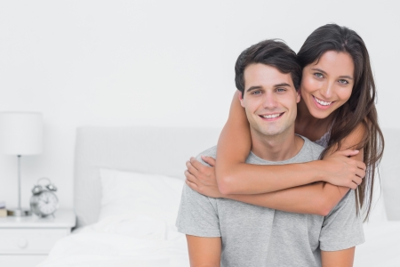 man long hair: Woman embracing her partner in bed Stock Photo