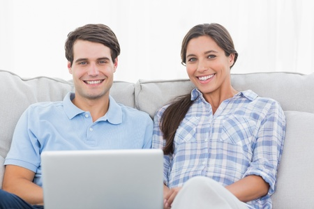 Couple resting with a laptop sat on a couch photo